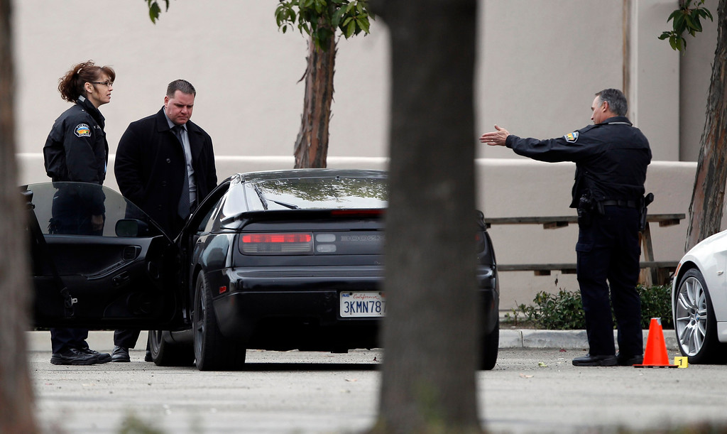 Description of . Police authorities process a black car, next to a stolen white car (R), in the parking lot of a Tustin computer store after a gunman went on a shooting spree in suburban southern California February 19, 2013REUTERS/Alex Gallardo