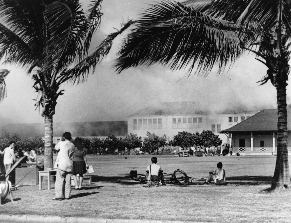 Description of . In this Dec. 7, 1941, file photo, students of the Lunalilo High School in the Waikiki district of Honolulu watch their school burn after the roof of the main building, at center, was hit by a bomb during the Japanese attack on Pearl Harbor, Hawaii.  (AP Photo/File)