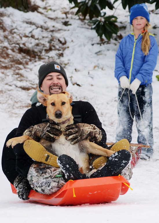 Description of . Bryan Hancock gives his dog Roy a ride on a sled down his driveway off of Ridgewood Drive in Goldsboro, N.C.,  Wednesday afternoon, Jan. 29, 2014. (AP PHOTO/News-Argus, Casey Mozingo)
