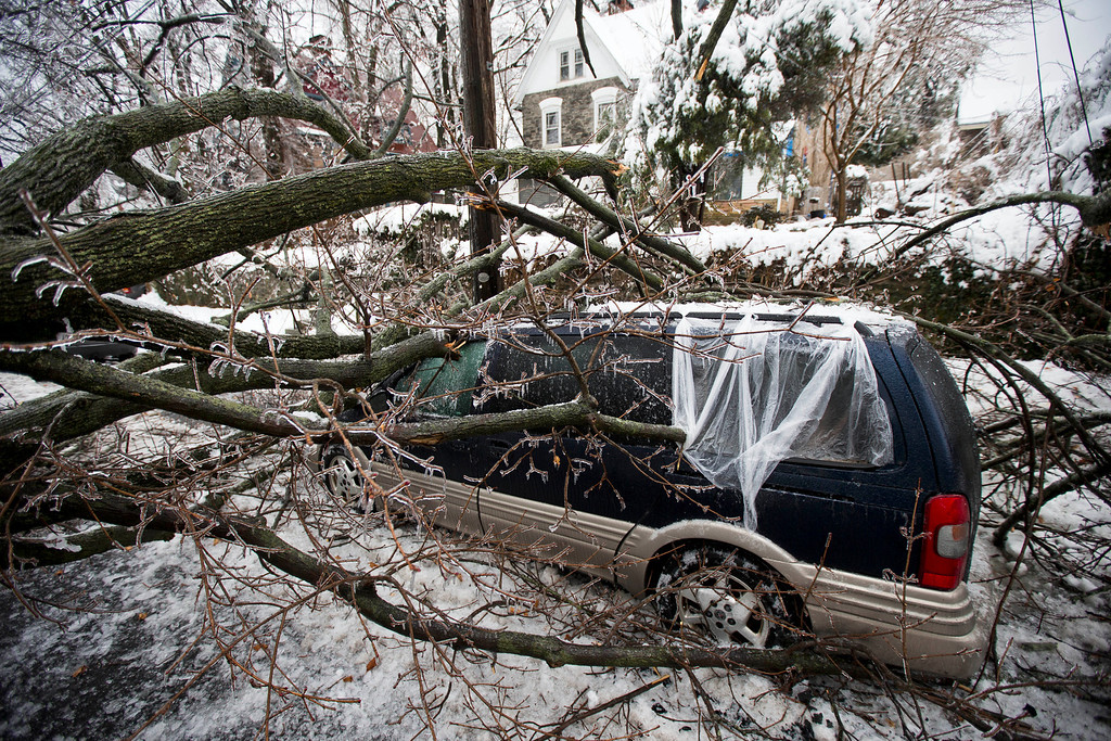 Description of . A downed tree covered in ice lays atop a minivan after a winter storm Wednesday, Feb. 5, 2014, in Philadelphia.  (AP Photo/Matt Rourke)