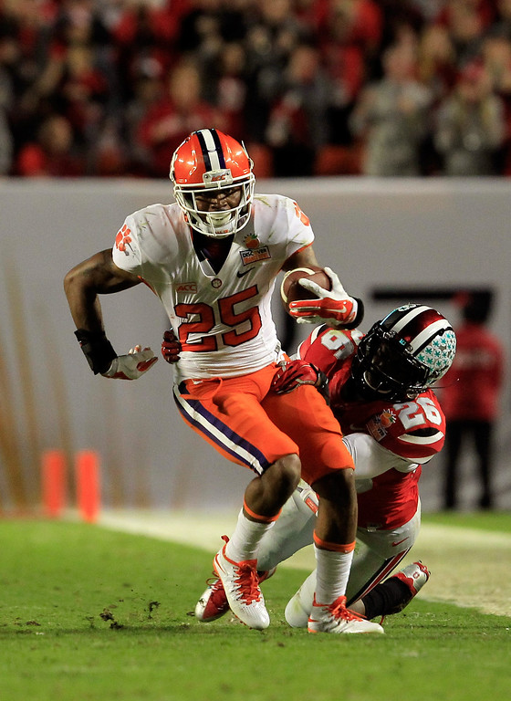 Description of . MIAMI GARDENS, FL - JANUARY 03:  Roderick McDowell #25 of the Clemson Tigers tries to convert a fourth down against Armani Reeves #26 of the Ohio State Buckeyes in the second quarter during the Discover Orange Bowl at Sun Life Stadium on January 3, 2014 in Miami Gardens, Florida.  (Photo by Chris Trotman/Getty Images)