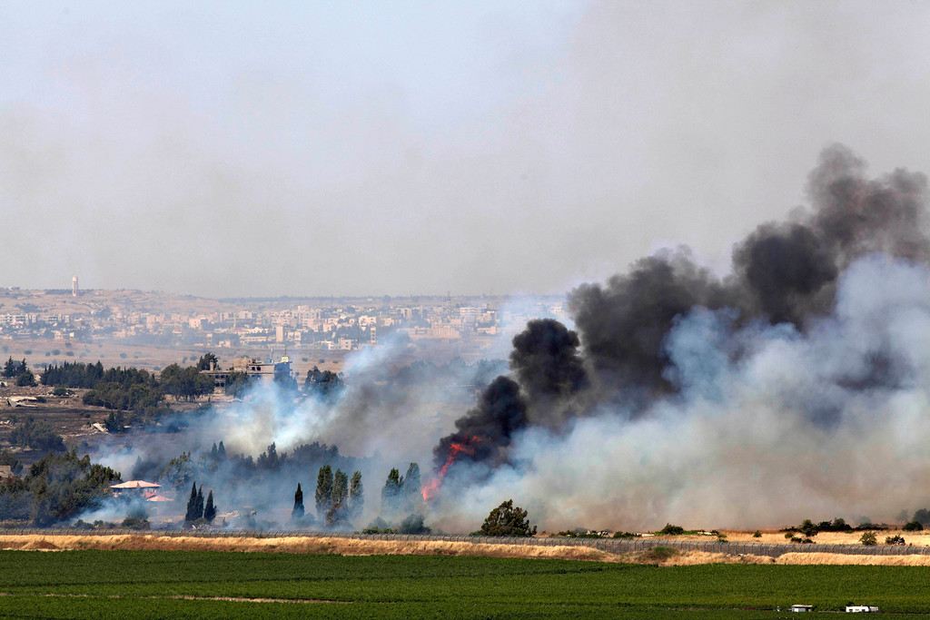 Description of . Smoke rises from a fire as a result of fighting in the the Syrian village of Quneitra near the border with Israel, as seen from an observatory near the Quneitra crossing, Thursday, June 6, 2013. Syrian rebels on Thursday captured a crossing point along a cease-fire line with Israel in the contested Golan Heights, a development that could deepen Israeli concerns over the growing role of Islamic radicals in the civil war near its northern frontier.(AP Photo/Sebastian Scheiner)