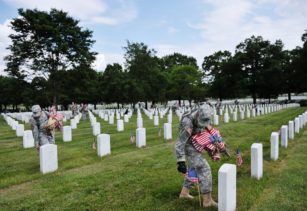 Description of . Staff Sergeant Joelle Monroe (R) of the Third US Infantry Regiment, The Old Guard, place flags in front of a grave at Arlington National Cemetery on May 23, 2013 in Arlington, Virginia ahead of Memorial Day.  AFP PHOTO/Mandel NGAN/AFP/Getty Images