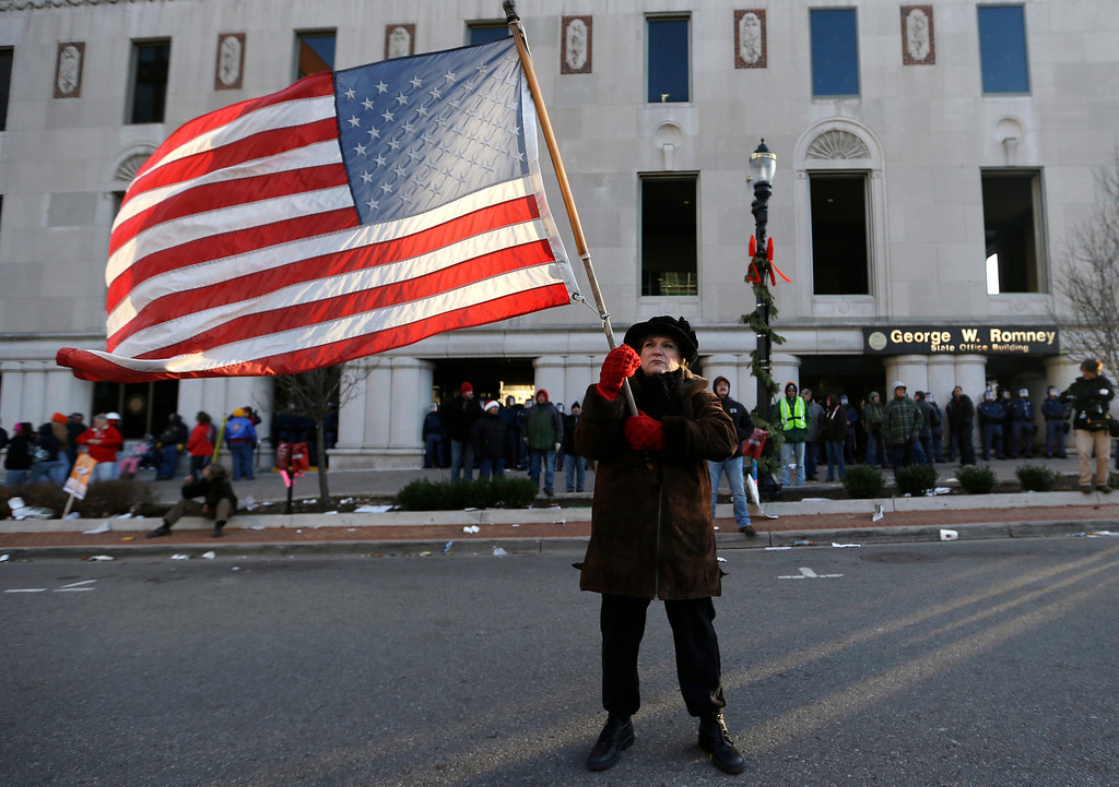 . Protester Paula Merwin, of Leslie, Mich., stands with an American flag outside the George W. Romney State Building, where Gov. Snyder has an office in Lansing, Mich., Tuesday, Dec. 11, 2012. The crowd is protesting right-to-work legislation passed last week. Michigan could become the 24th state with a right-to-work law next week. Rules required a five-day wait before the House and Senate vote on each other\'s bills; lawmakers are scheduled to reconvene Tuesday and Gov. Snyder has pledged to sign the bills into law. (AP Photo/Paul Sancya)