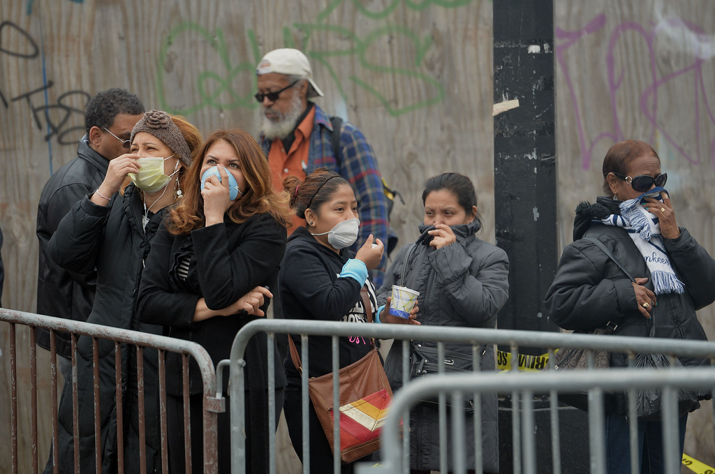 Description of . Bystanders cover their faces against the smoke as they watch the scene of an explosion and building collapse at Park Avenue and East 116th Street March 12, 2014 in the Harlem section of New York.   AFP PHOTO/Stan HONDA/AFP/Getty Images