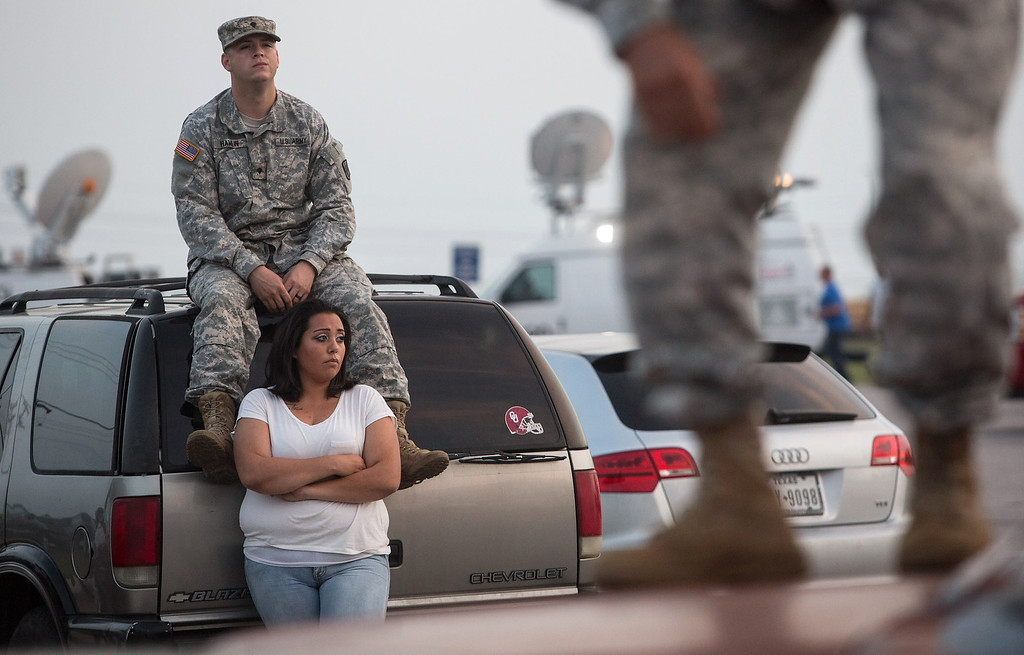 Description of . Lucy Hamlin and her husband, Spc. Timothy Hamlin, wait for permission to re-enter the Fort Hood military base, where they live, following a shooting on base on Wednesday, April 2, 2014, in Fort Hood, Texas. One person was killed and 14 injured in the shooting, and officials at the base said the shooter is believed to be dead. The details about the number of people hurt came from two U.S. officials who spoke on condition of anonymity because they were not authorized to discuss the information by name. (AP Photo/ Tamir Kalifa)