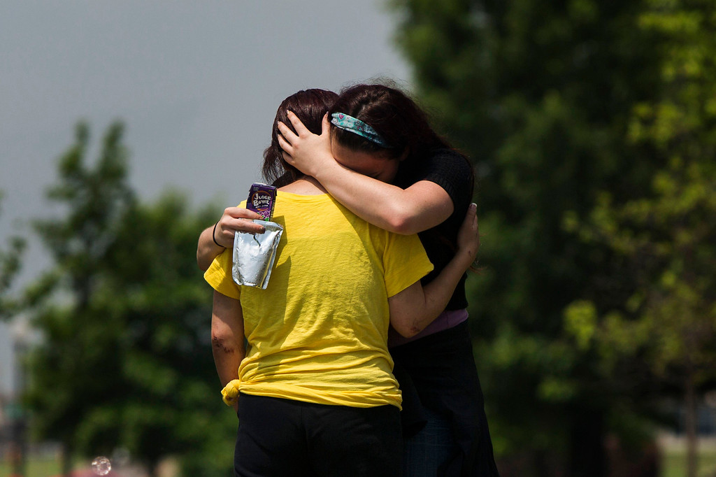 Description of . Michelle Gonzalez (L), a 3rd grade teacher at the Plaza Towers elementary school, embraces friend Ashley Gentry after being overcome by pain from injuries incurred during the recent tornado as she departs a ceremonial last day of the school year at the Eastlake Elementary School in Moore, Oklahoma, May 23, 2013. Seven students were killed at Plaza Towers Elementary when a tornado packing winds of 200 miles (320 km) per hour slammed into the building on Monday afternoon just before school was to have let out. The massive tornado obliterated sections of Moore, Oklahoma, leaving 24 dead on May 20. REUTERS/Lucas Jackson