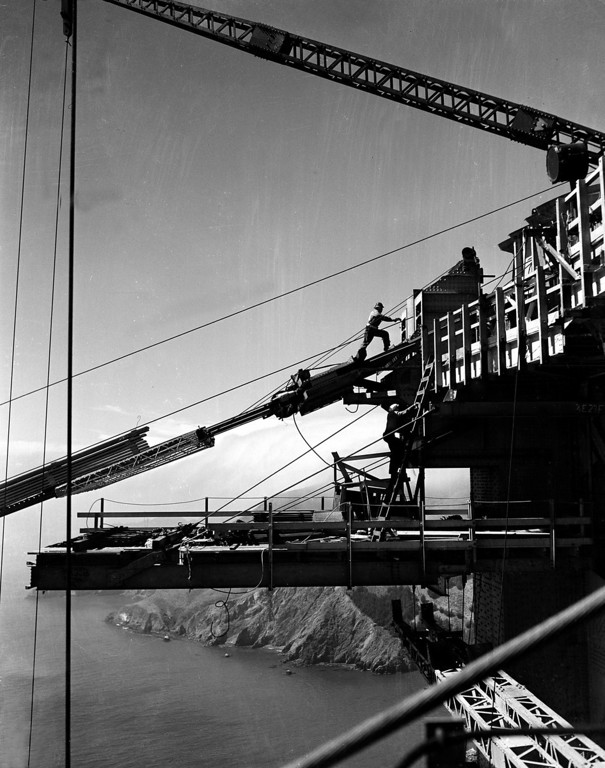 Description of . Workers at the top of the tower, which will support the $35,000,000 suspension bridge, are shown during construction of one of the catwalks for the Golden Gate Bridge in San Francisco, Ca., Oct. 17, 1935.  Below in background is the Marin County shore, which will be connected to San Francisco by the bridge.  (AP Photo)