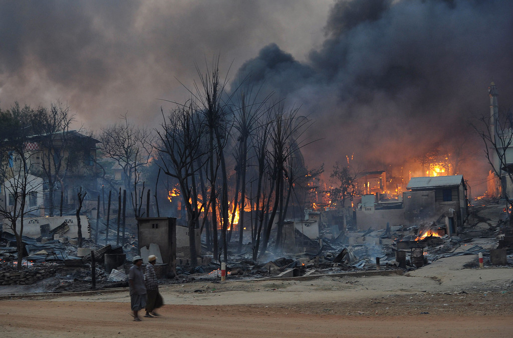 Description of . Residents walk past buildings burning in riot-hit Meiktila, central Myanmar, on March 21, 2013.    Than WIN/AFP/Getty Images