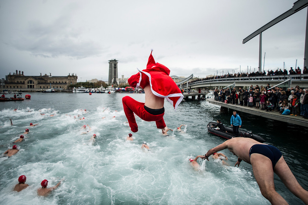 Description of . BARCELONA, SPAIN - DECEMBER 25:  A competitor in Christmas fancy dress jumps into the sea during the 104rd Barcelona Traditional Christmas Swimming Cup at the Old Harbour of Barcelona on December 25, 2013 in Barcelona, Spain. The Copa Nadal is organised by the Barcelona Swimming Club and involves competitors swimming across some 200 metres of water in the harbour. Launched in 1908 the event has only been suspended three times when the Spanish Civil War interrupted proceedings between 1936 and 1938.  (Photo by David Ramos/Getty Images)