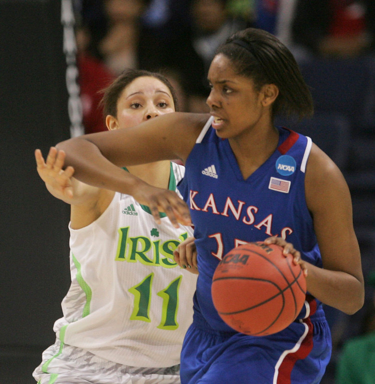 Description of . Kansas forward Chelsea Gardner (15) tries to fend off Notre Dame forward Natalie Achonwa (11) during the first half a regional semi-final of the NCAA college basketball tournament Sunday, March31, 2013, in Norfolk, Va.  (AP Photo/Jason Hirschfeld)