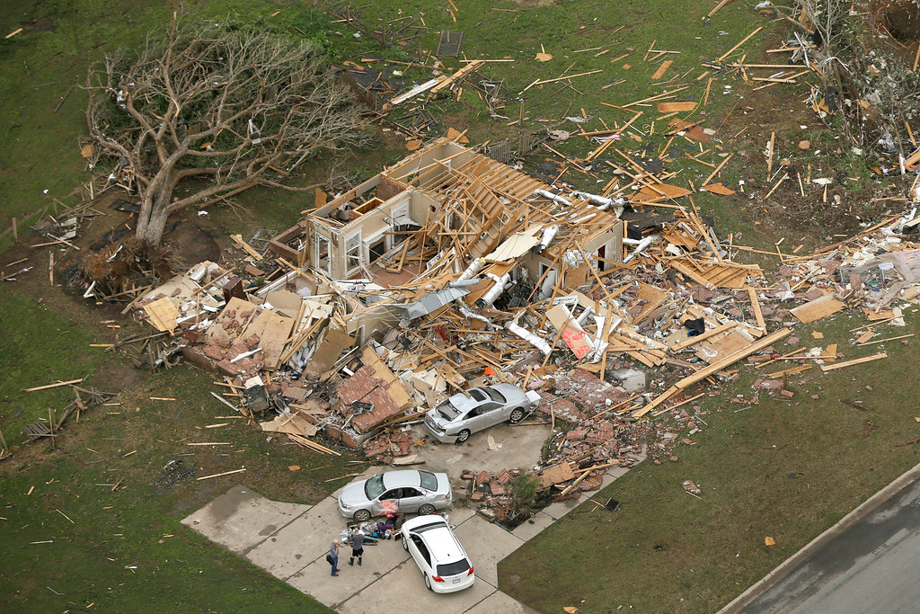 Description of . Two men stand in front of a destroyed house in Mayflower, Ark., Monday, April 28, 2014, after a tornado struck the town late Sunday. (AP Photo/Danny Johnston)