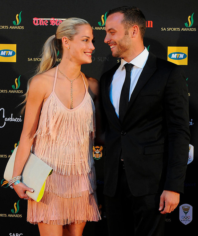 "Description of . South African ""Blade Runner\"" Oscar Pistorius (R) smiles with his girlfriend, model Reeva Steenkamp at an awards ceremony in Johannesburg November 4, 2012. Pistorius a double amputee who became one of the biggest names in world athletics, was charged on February 14, 2013 with shooting dead Steenkamp at his home in Pretoria. Picture taken November 4, 2012.   REUTERS/Frennie Shivambu/JustusMedia"