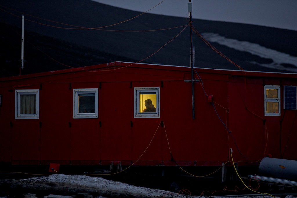 Description of . In this Jan. 24, 2015 photo, a scientist stands behind a window on the Spanish base Gabriel de Castilla on Deception Island, part of the South Shetland Islands archipelago in Antarctica. If experts are right, and the West Antarctic ice sheet has started melting irreversibly, what happens here will determine if cities such as Miami, New York, New Orleans, Guangzhou, Mumbai, London and Osaka will have to regularly battle flooding from rising seas. (AP Photo/Natacha Pisarenko)