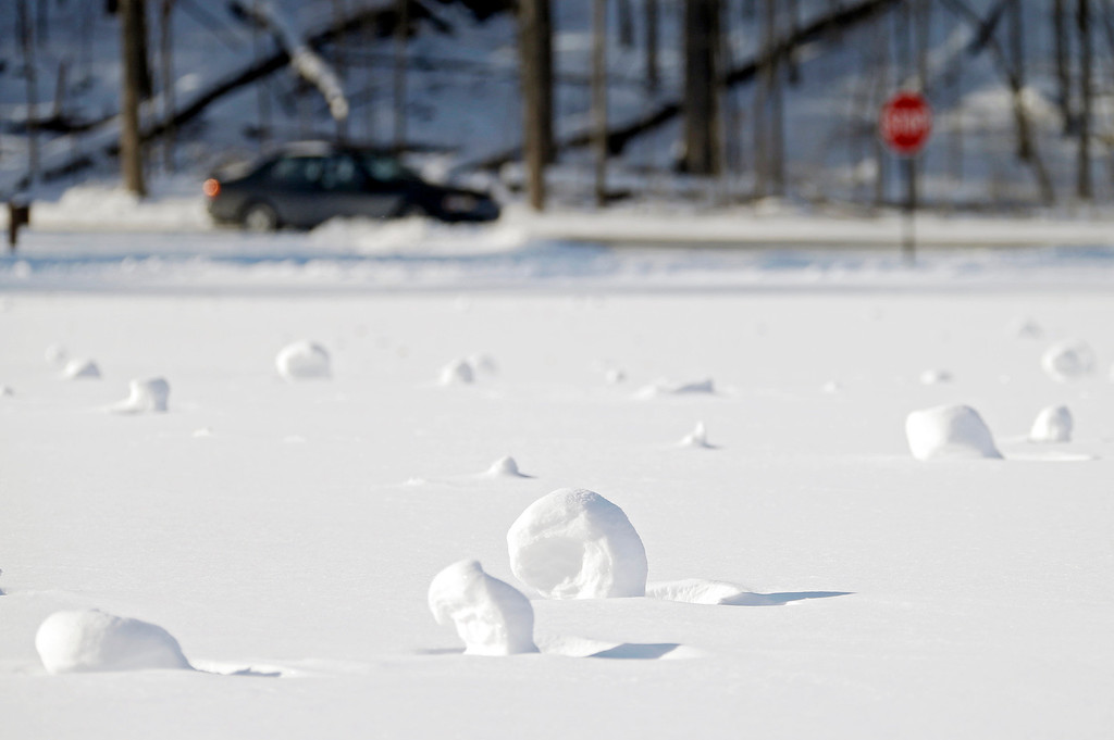 Description of . Snow rollers dot a field at the Cleveland Metroparks Mastic picnic area Tuesday, Jan. 28, 2014, in Fairview Park, Ohio. The snowballs are formed when high winds roll accumulated snow across open areas. The National Weather Service has placed most of Ohio under a wind chill warning until Wednesday. (AP Photo/Mark Duncan)