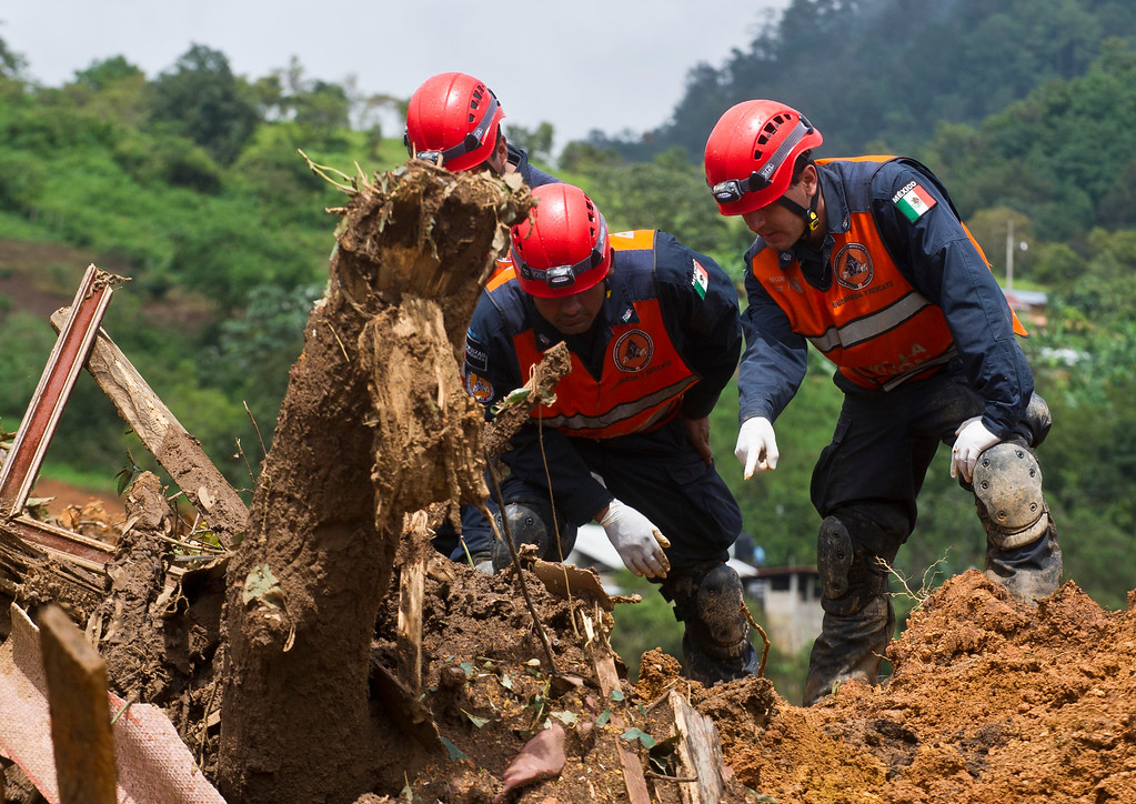 Description of . Mexico's Federal Police personnel search for bodies on the site of a landslide in La Pintada, state of Guerrero, Mexico, on September 19, 2013 as heavy rains hit the country. AFP PHOTO/RONALDO  Schemidt/AFP/Getty Images