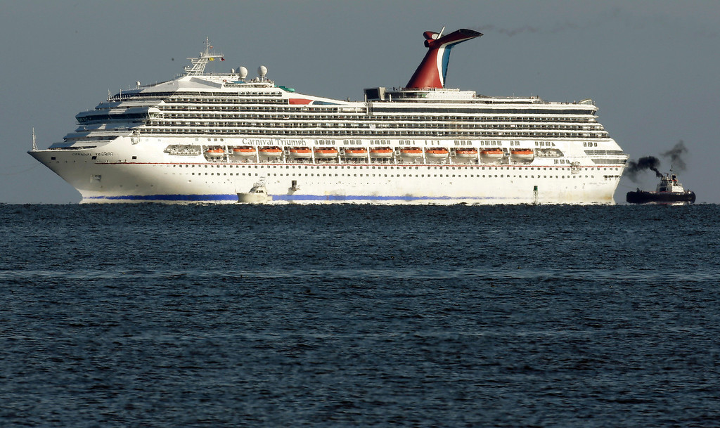 Description of . The cruise ship Carnival Triumph is towed towards Mobile Bay near Dauphin Island, Ala., Thursday, Feb. 14, 2013.  (AP Photo/Dave Martin)