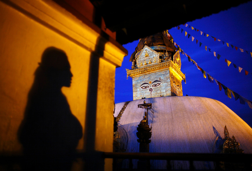 Description of . The shadow of a woman is cast on the wall of a monastery as she looks on toward the Swayambhunath Stupa in Kathmandu, Nepal August 23, 2012. The Swayambhunath Stupa is a collection of shrines and temples. REUTERS/Navesh Chitrakar