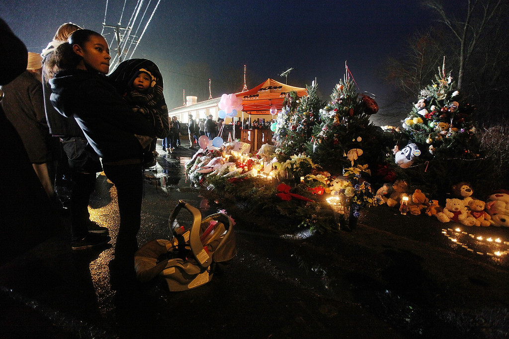 Description of . NEWTOWN, CT - DECEMBER 16:  Isabel Lebron holds son Izaiah Taylor at a memorial with donated Christmas trees honoring victims near the school on the first Sunday following the mass shooting at Sandy Hook Elementary School on December 16, 2012 in Newtown, Connecticut. U.S. President Barack Obama visited the grief stricken town today.  (Photo by Mario Tama/Getty Images)