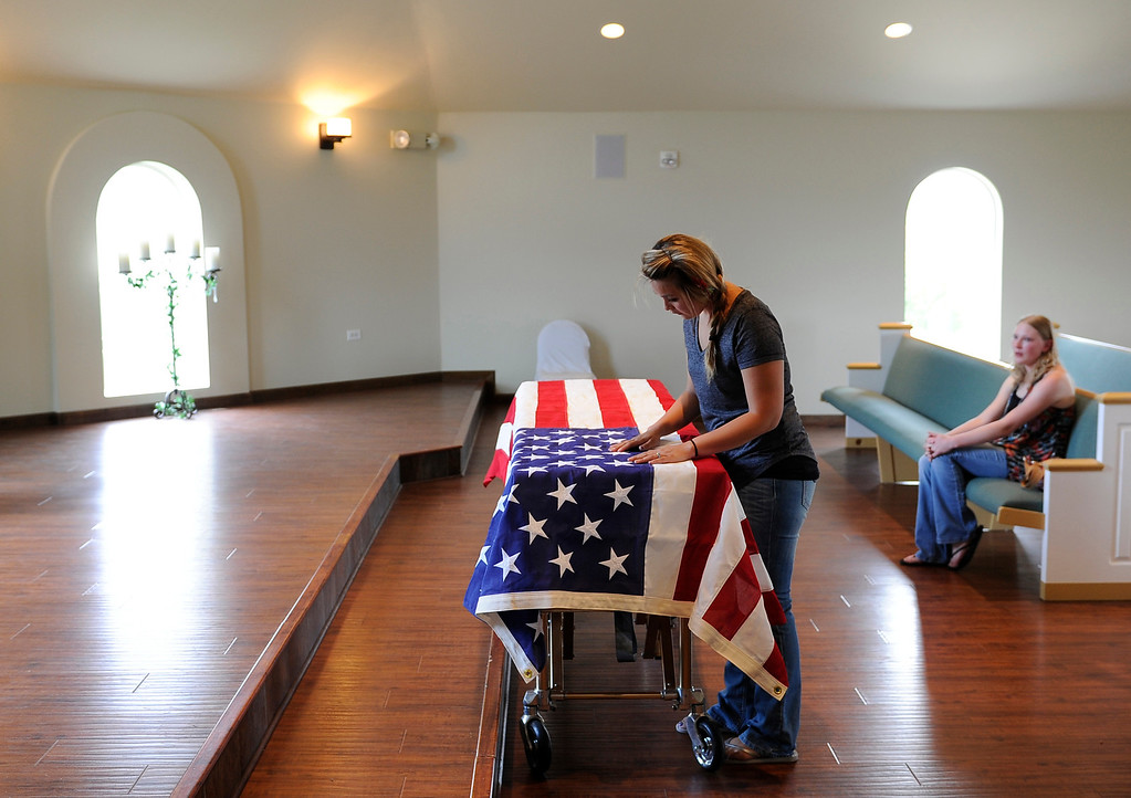 Description of . Chantel Blunk cleans lint off the flag draped over her husband Johnathan Blunk's casket at Apollo and Three Tree Chapel in Littleton on Friday, July 27, 2012. Blunk's casket was being prepared to be flown to Reno, Nevada for his full military funeral. Blunk, a five-year U.S. Navy veteran, was killed when James Holmes opened fire at a crowded movie theater. RJ Sangosti, The Denver Post