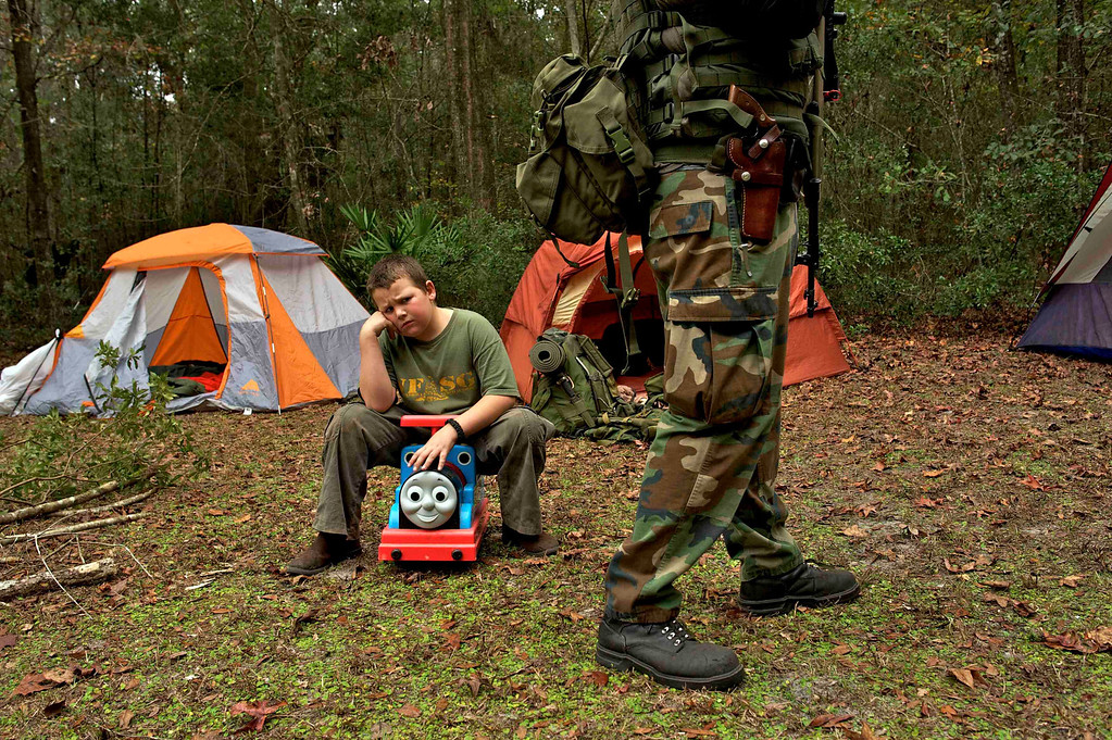 ". A young boy sits on a child\'s toy and sulks because his sister got to carry the rifle that he wanted to carry as members of the North Florida Survival Group gather for a field training exercise in Old Town, Florida, December 8, 2012.The group trains children and adults alike to handle weapons and survive in the wild. The group passionately supports the right of U.S. citizens to bear arms and its website states that it aims to teach ""patriots to survive in order to protect and defend our Constitution against all enemy threats\"". Picture taken December 8, 2013.   REUTERS/Brian Blanco"