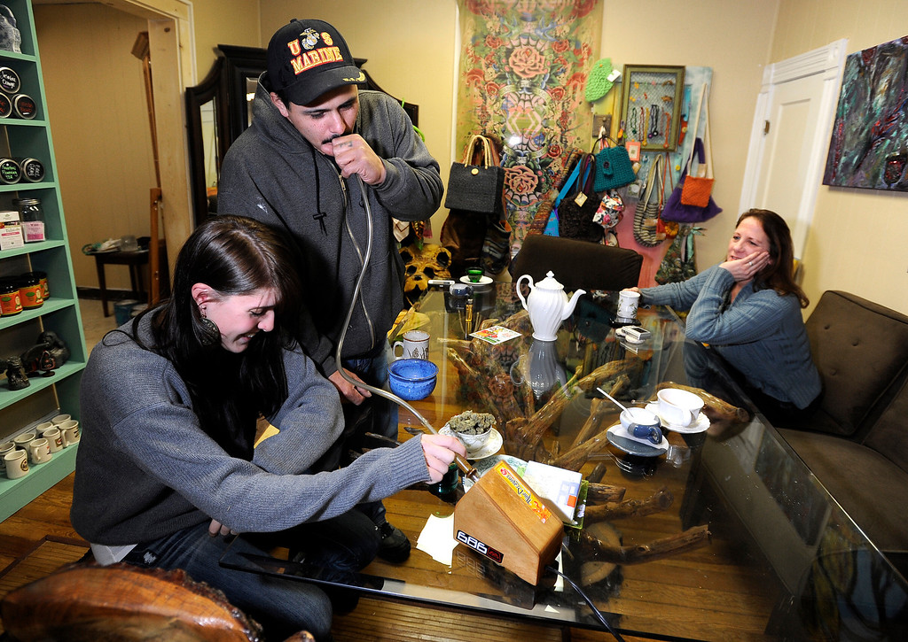Description of . Rudy Capuchio, of Lafayette, center, takes a hit of marijuana from a vaporizer while smoking with Kyrie Wozab, of Louisville, left, and Heidi Perreria, of Lafayette, right, on Wednesday, Jan. 2, at The Hive Co-Op Cannabis Club in Lafayette. Jeremy Papasso/Boulder Daily Camera