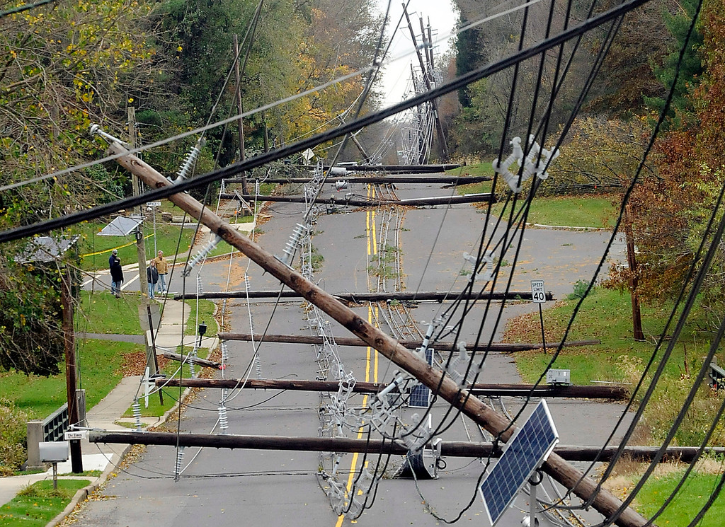 Description of . In this Thursday, Nov. 1, 2012 photo, downed utility poles and wires lie along Bull Run Road in Hopewell Township, N.J, three days after Hurricane Sandy swept through the region, leaving many without power. (AP Photo/The Trentonian, Jackie Schear)