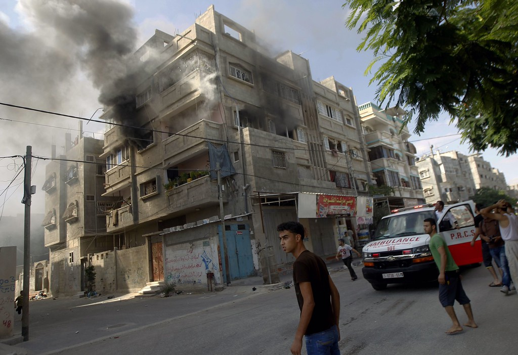 Description of . Palestinians watch smoke rising from a building following an Israeli strike on Rafah, in the southern Gaza Strip, on July 31, 2014. At least 10 people were killed in Israeli strikes on central and southern Gaza bringing the Palestinian death toll to 1,374 on day 24 of the conflict.  AFP PHOTO / SAID KHATIB/AFP/Getty Images