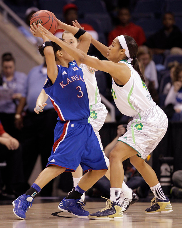 Description of . Notre Dame guard Skylar Diggins, right, pressures Kansas guard Angel Goodrich (3) during a regional semi-final of the NCAA college basketball tournament  Sunday, March 31,2013, in Norfolk, Va.  Notre Dame won 93-63. (AP Photo/Steve Helber)