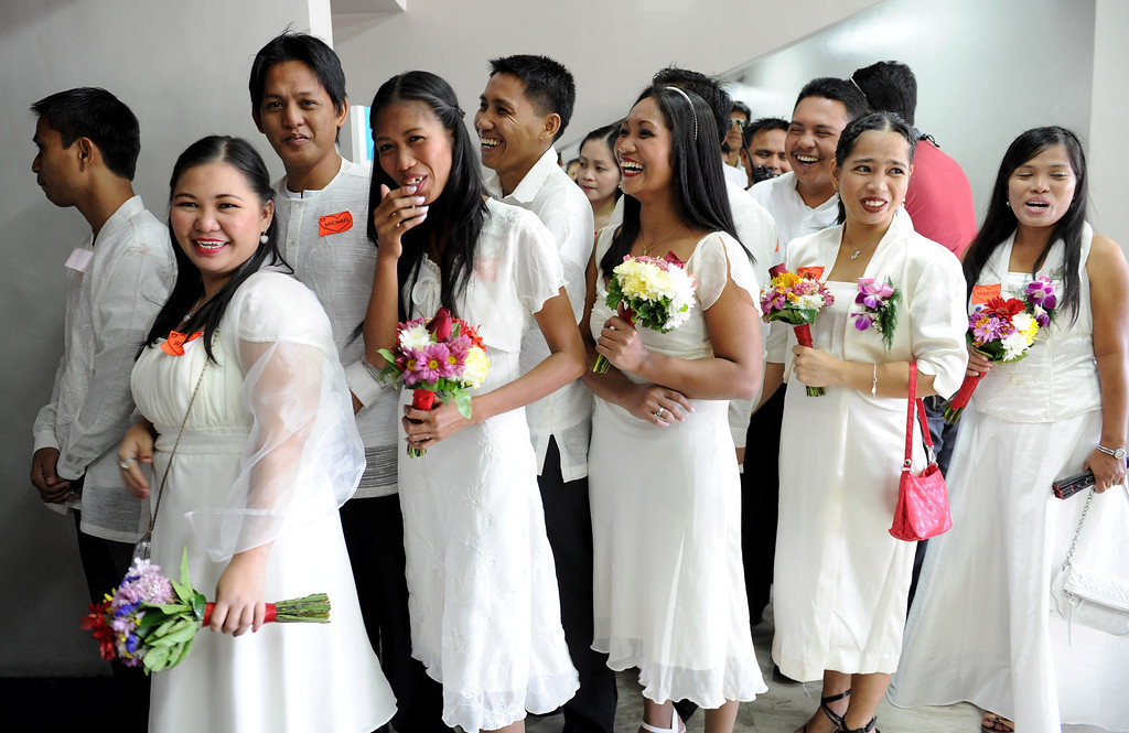 Description of . Couples stand in a queue at a gymnasium for a mass wedding in Manila on February 14, 2013. Some 400 couples exchanged vows inside a packed gymnasium on the outskirts of Manila's Makati financial district, as a school band played love songs that drowned out the heavy traffic outside. AFP PHOTO / Jay DIRECTO/AFP/Getty Images