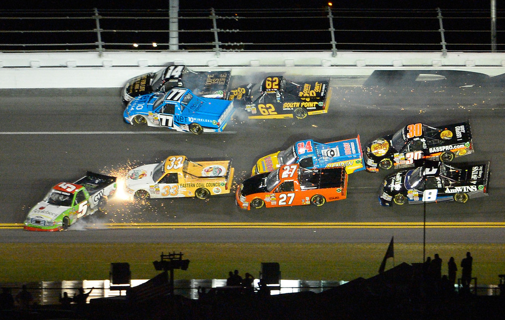 Description of . A wreck between Turns 3 and 4 ensnares Tim George Jr. (5), John King (33), Jeff Agnew (27), Chris Fontaine (84), Brennan Newberry (14), German Quiroga (77), Brendan Gaughan (62), Ryan Truex (30), and Max Gresham (8) on Lap 53 during the NASCAR Truck Series auto race at Daytona International Speedway in Daytona Beach, Fla., Friday, Feb. 22, 2013. (AP Photo/Phelan M. Ebenhack)