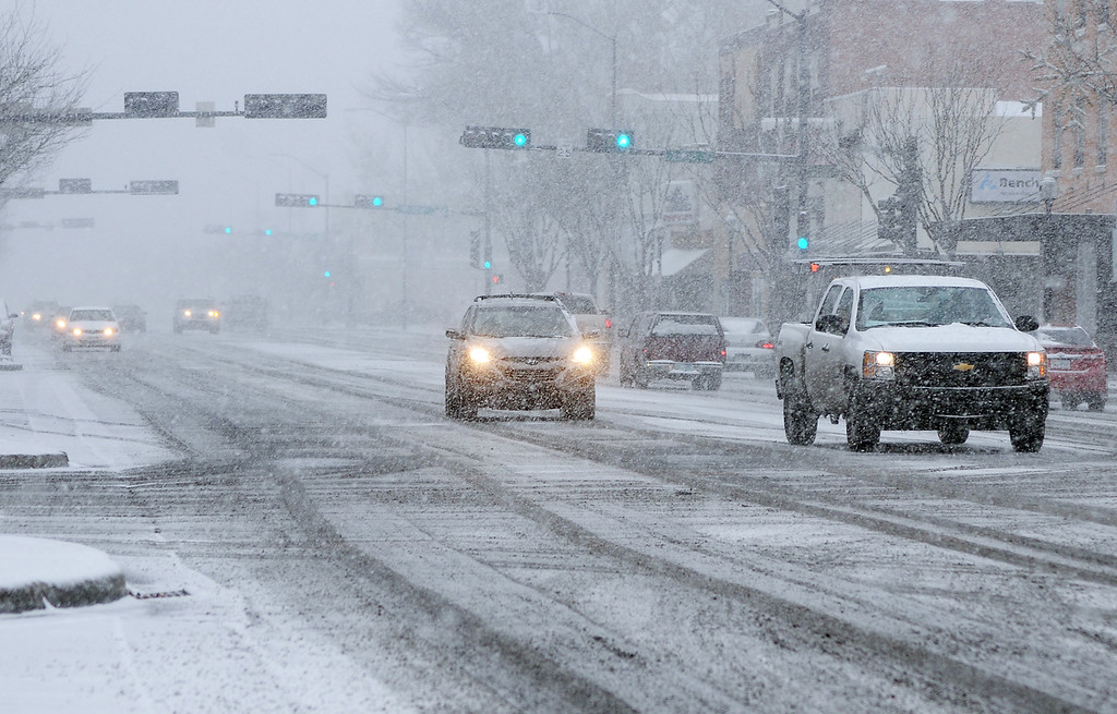 Description of . In this photo taken Thursday, Dec. 5, 2013, motorists proceed cautiously along Main Street as snow falls in downtown Roswell, N.M. (AP Photo/Roswell Daily Record, Mark Wilson)