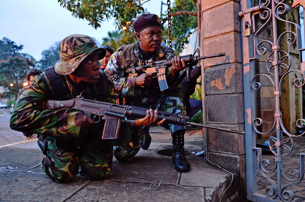 Description of . Kenyan soldiers take cover after heavy gunfire near Westgate mall in Nairobi on September 23, 2013. Kenyan Defense troops remain inside the mall, in a standoff with Somali militants after they laid siege to the shopping centre shooting and throwing grenades as they entered. Somali Shebab militants on September 23 threatened to kill hostages they are holding in the Nairobi shopping mall as Kenyan troops move to end their siege. AFP PHOTO / CARL DE SOUZA/AFP/Getty Images