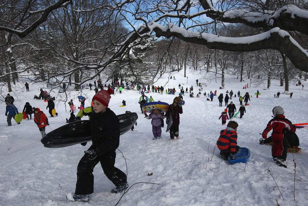 . NEW YORK, NY - FEBRUARY 09:  Children sled in Central Park on February 9, 2013 in New York City. The park received almost a foot of snow, as New York was spared the worst of the massive snow storm that hit the U.S. Northeast.  (Photo by John Moore/Getty Images)