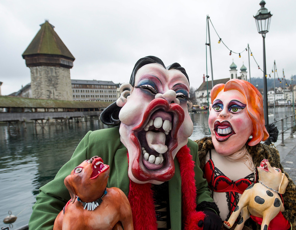 Description of . Carnival participants pose for pictures during the carnival procession (Fasnacht), in the historic center of Lucerne, Switzerland, 27 February 2014.  EPA/SIGI TISCHLER