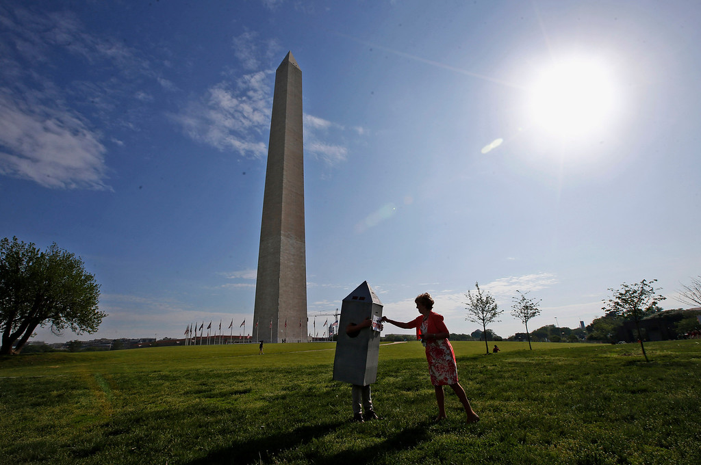 . Vicki Dixon, an Interior Department employee, right, helps her colleague Steven Avila, with his Washington Monument costume at the Washington Monument in Washington, Monday, May 12, 2014, ahead of a ceremony to celebrate its re-opening. The monument, which sustained damage from an earthquake in August 2011, is reopening to the public today. Avila made the costume to show his support for the re-opening of the monument. (AP Photo)