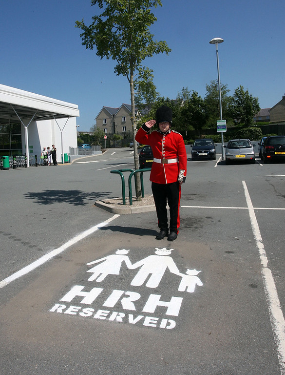 Description of . A man dressed as a member of the queen\'s guard poses beside a parking space reserved for the prospective prince or princess on July 11, 2013, as the Duke and Duchess of Cambridge prepare for the birth of their first child. The supermarket, on the island of Anglesey is situated near to the home that the Duke and Duchess of Cambridge share. (Photo by Richard Birch/Asda via Getty Images)