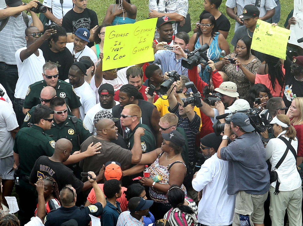 Description of . Deputies try to maintain calm after demonstrators become involved in a shouting match outside the Seminole County Criminal Justice Center during jury deliberations in the trial of George Zimmerman , in Sanford, Fla., Saturday, July  13, 2013. Zimmerman has been charged with the 2012 shooting death of Trayvon Martin.(AP Photo/Orlando Sentinel, Joe Burbank, Pool)