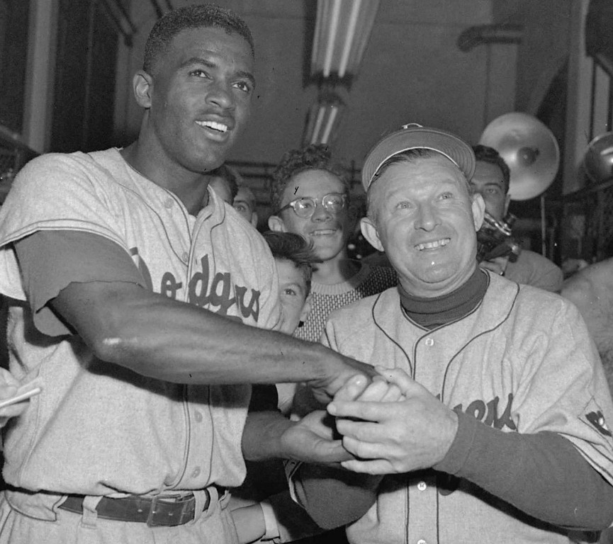 Description of . Brooklyn Dodgers\' Jackie Robinson, left,  is congratulated on his game-winning home run by manager Charley Dressen on  September 30, 1951 in Philadelphia. Robinson broke the color barrier and changed baseball forever. (AP Photo/file)