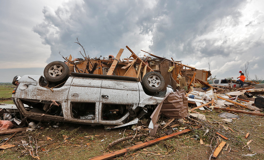 . A demolished home with the car flipped over is all that remains left behind in the damage from the tornado that hit the area near 149th and Drexel on Monday, May 20, 2013 in Oklahoma City, Okla. (AP Photo/ The Oklahoman, Chris Landsberger)