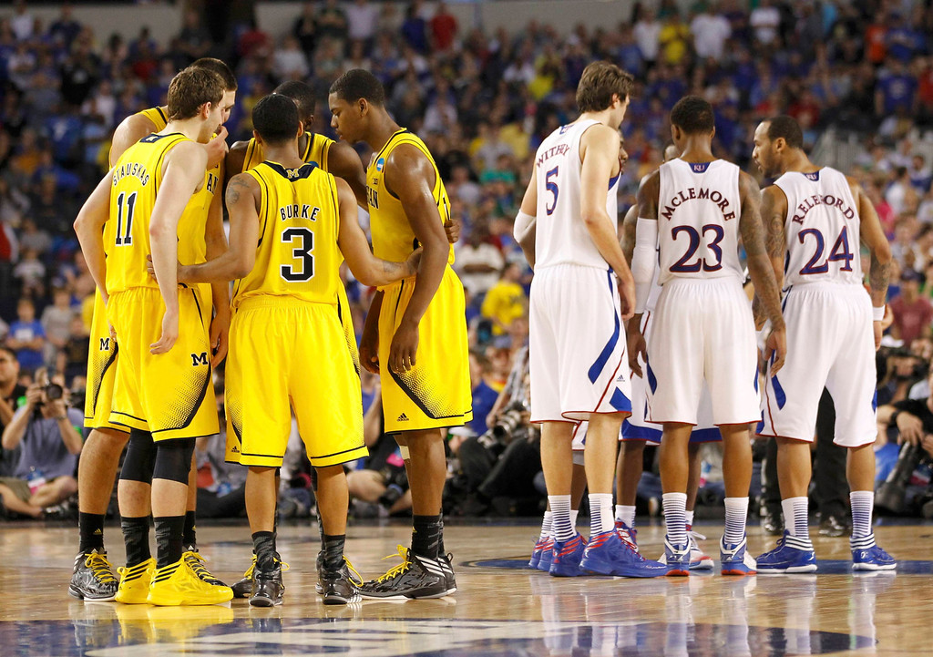 Description of . The Michigan Wolverines and Kansas Jayhawks talk during overtime in their South Regional NCAA men\'s basketball game in Arlington, Texas March 29, 2013. REUTERS/Mike Stone