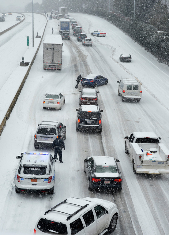 Description of . Traffic along Independence Boulevard near Hawthorne Lane crawls along the slick roadway as a winter storm hits   Wednesday, Feb. 12, 2014, in Charlotte, N.C. (AP Photo/The Charlotte Observer, Davie Hinshaw)