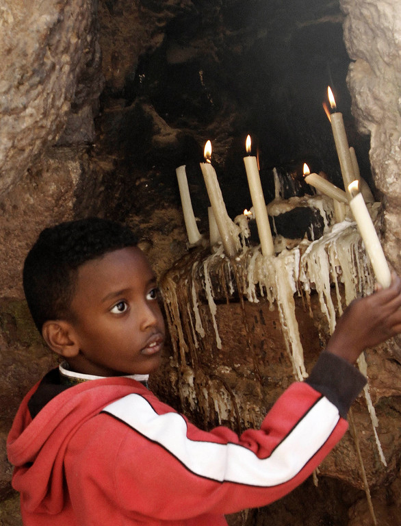 Description of . A Christian boy lights candles during Christmas mass at a Church in Khartoum, Sudan, Wednesday, Dec. 25, 2013. (AP Photo/Abd Raouf)
