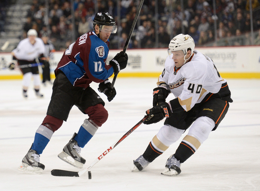 Description of . DENVER, CO. - FEBRUARY 06: Jordan Hendry (40) of the Anaheim Ducks gains control of the puck in front of Chuck Kobasew (12) of the Colorado Avalanche during the third period February 6, 2013 at Pepsi Center. The Colorado Avalanche fall to the Anaheim Ducks  3-0 during NHL action. (Photo By John Leyba / The Denver Post)