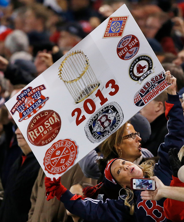 Description of . A fan poses with a makeshift championship poster during Game 6 of baseball's World Series between the St. Louis Cardinals and the Boston Red Sox Wednesday, Oct. 30, 2013, in Boston. (AP Photo/Elise Amendola)