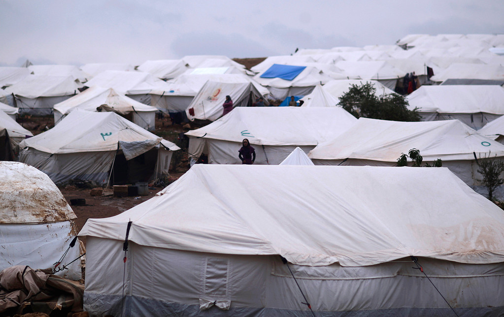 Description of . In this Monday, Dec. 10, 2012 photo, Syrians who fled their homes stand by their tents at a camp for displaced Syrians, in the village of Atmeh, Syria. This tent camp sheltering some of the hundreds of thousands of Syrians uprooted by the country's brutal civil war has lost the race against winter: the ground under white tents is soaked in mud, rain water seeps into thin mattresses and volunteer doctors routinely run out of medicine for coughing, runny-nosed children. (AP Photo/Muhammed Muheisen)