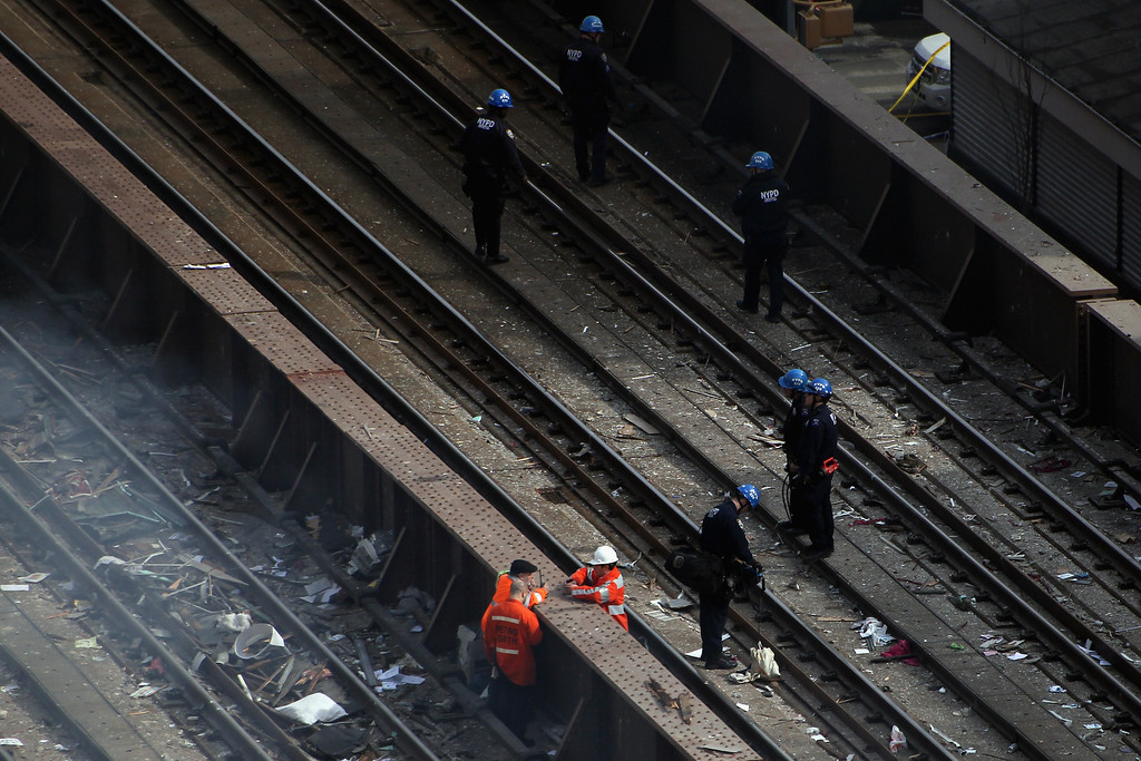 Description of . Emergency personnel stand on the Metro-North train tracks as they respond to a five-alarm fire and building collapse at 1646 Park Ave in the Harlem neighborhood of Manhattan March 12, 2014 in New York City. (Photo by Justin Heiman/Getty Images)