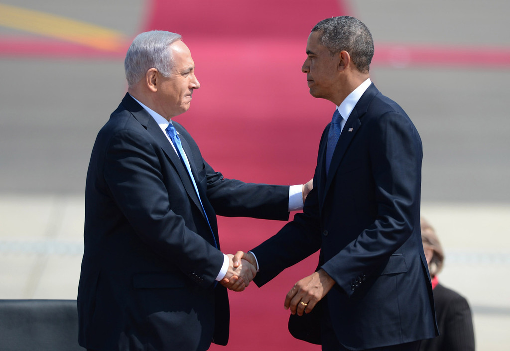 Description of . In this handout image supplied by the Government Press Office of Israel (GPO), US President Barack Obama is welcomed by Israeli President Benjamin Nethanyahu at Ben Gurion International Airport on March 20, 2013 near Tel Aviv, Israel.  This will be Obama's first visit as President to the region, and his itinerary will include meetings with the Palestinian and Israeli leaders as well as a visit to the Church of the Nativity in Bethlehem. (Photo by Kobi Gideon /GPO via Getty Iimages)