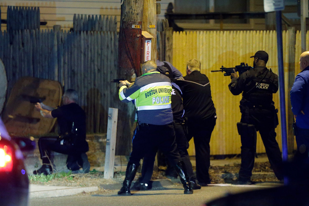 Description of . Police officers aim their weapons Friday, April 19, 2013, in Watertown, Mass. A tense night of police activity that left a university officer dead on campus just days after the Boston Marathon bombings and amid a hunt for two suspects caused officers to converge on a neighborhood outside Boston, where residents heard gunfire and explosions.(AP Photo/Matt Rourke)