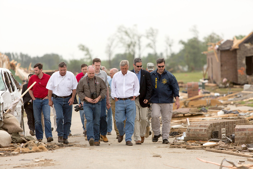 Description of . Arkansas Gov. Mike Beebe, third from right, surveys the tornado damage along Aspen Creek Drive in the Parkwood neighborhood off Naylor Road in Vilonia, Ark. after a tornado struck the town. Vilonia was hit hard Sunday after a tornado system ripped through several states in the central U.S. and left more than a dozen dead in a violent start to this year's storm season, officials said. (AP Photo/Karen E. Segrave)